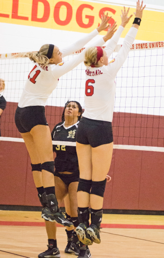 Sophomore Nicole Malouhos and senior Stephanie Sikorski leap to block an incoming spike.