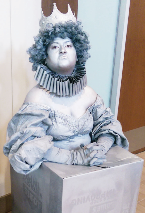 """A human statue perched outside of the Quad cafeteria in the UC promoting this weekend's """"Big Fish."""""""